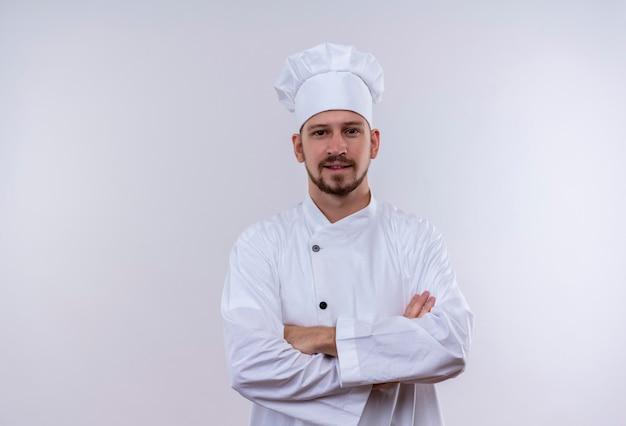 Professioneller männlicher koch kocht in der weißen uniform und im kochhut mit den verschränkten armen, die zuversichtlich über weißem hintergrund stehen