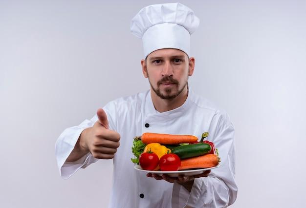 Professioneller männlicher koch kocht in der weißen uniform und kochhut, die platte mit gemüse hält, das daumen oben zeigt lächelnd steht über weißem hintergrund