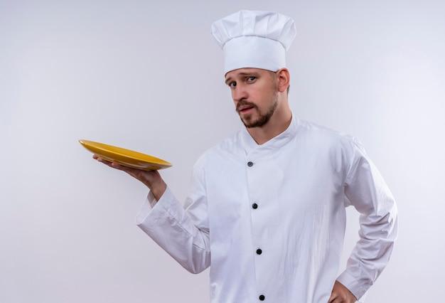 Professioneller männlicher kochkoch in der weißen uniform und im kochhut, der eine leere platte mit dem sicheren blick zeigt, der über weißem hintergrund steht