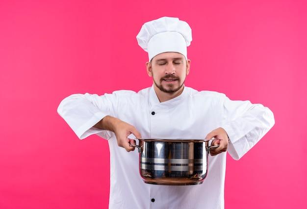 Professioneller männlicher kochkoch in der weißen uniform und im kochhut, der eine pfanne hält, atmen den angenehmen geruch des essens ein, das über rosa hintergrund steht