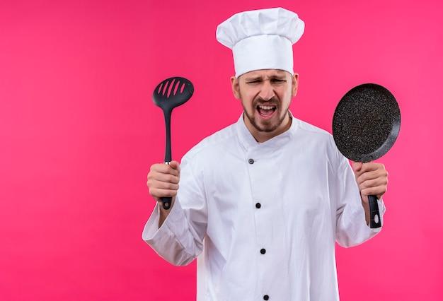Professioneller männlicher kochkoch in der weißen uniform und im kochhut, der eine pfanne und eine kelle hält, die enttäuscht und genervt über rosa hintergrund stehen