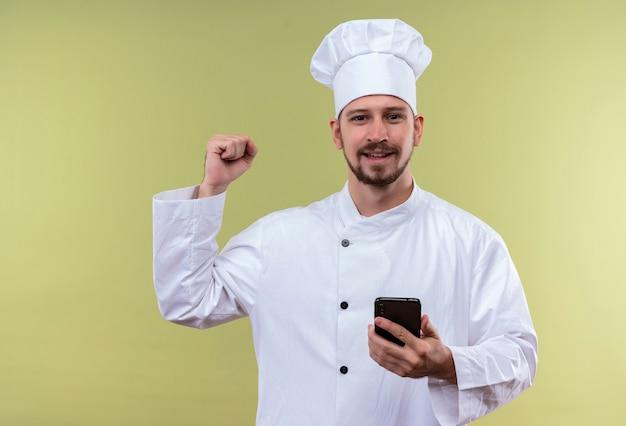 Professioneller männlicher kochkoch in der weißen uniform und im kochhut, der handy hält, das die faust glücklich und positiv erhebt, die seinen erfolg erfreut, der über grünem hintergrund steht