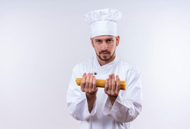 Professioneller männlicher kochkoch in der weißen uniform und im kochhut, der rohe spaghetti-nudeln demonstriert, die zuversichtlich stehen, über weißem hintergrund stehen