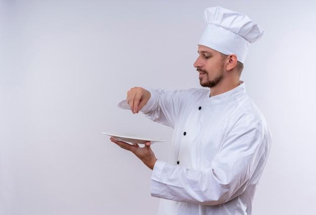 Professioneller männlicher kochkoch in der weißen uniform und im kochhut, der salz auf einem lächelnden teller über weißem hintergrund spritzt