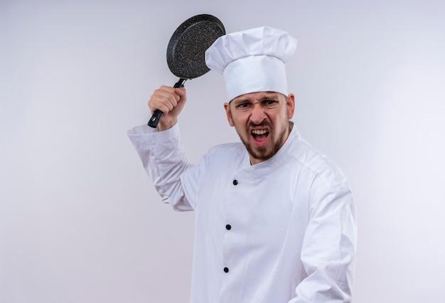 Professioneller männlicher kochkoch in der weißen uniform und im kochhut, die eine bratpfanne mit aggressivem ausdruck schwingen, der über weißem hintergrund steht