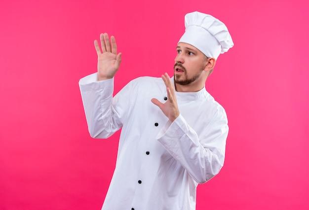 Professioneller männlicher kochkoch in weißer uniform und kochhut, der seine hände hochhält und erzählt, kommen nicht näher über rosa hintergrund