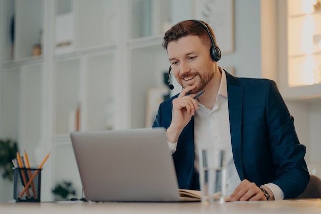 Professioneller männlicher operator arbeitet im callcenter verwendet headset- und laptop-computergespräche bei videoanrufen oder virtuelle webcam-veranstaltungen tragen formelle kleidung, posieren gegen gemütliches interieur und haben online-meetings