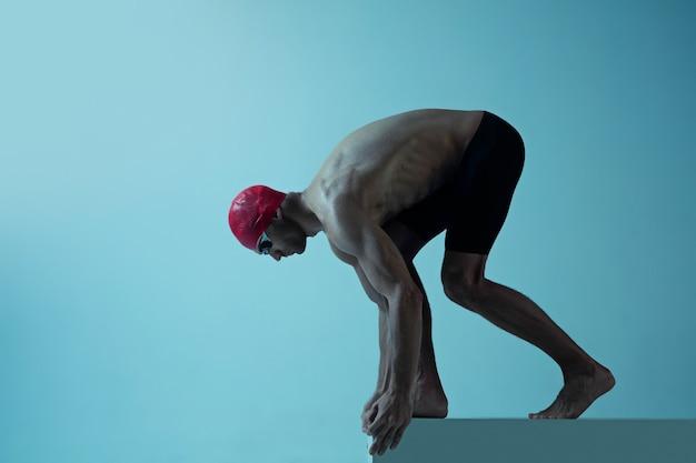 Professioneller männlicher schwimmer mit hut und brille in bewegung und action