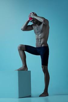 Professioneller männlicher schwimmer mit hut und schutzbrille in bewegung und aktion, gesundem lebensstil und bewegung