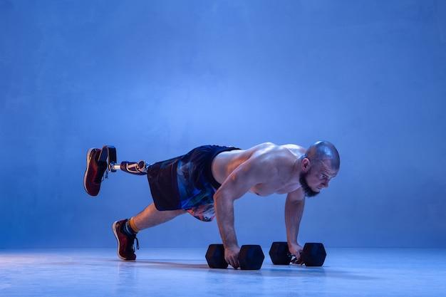 Professioneller männlicher sportler mit beinprothesentraining mit hanteln