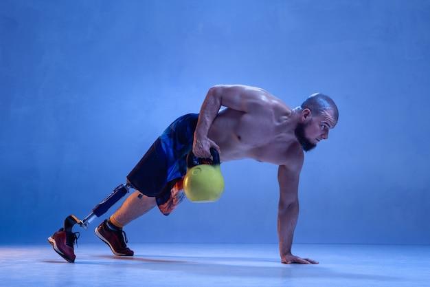 Professioneller männlicher sportler mit beinprothesentraining mit kettlebell