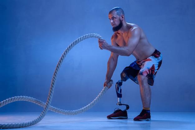 Professioneller männlicher sportler mit beinprothesentraining mit seilen in neon