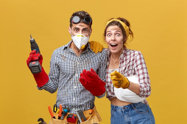 Professioneller männlicher techniker mit schutzbrille am kopf, schutzmaske und handschuhen, bohrmaschine mit werkzeuggürtel