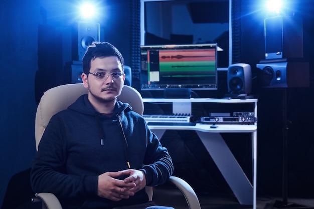 Professioneller männlicher tontechniker, der audio im aufnahmestudio mischt. musikproduktionstechnologie, die am mixer arbeitet