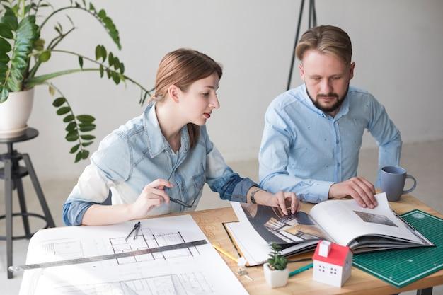 Professioneller männlicher und weiblicher architekt, der katalog beim arbeiten im büro schaut