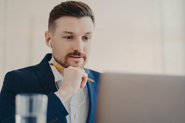 Professioneller männlicher unternehmer, der sich auf laptop konzentriert, verwendet kopfhörer, hört die notwendigen informationen an, beobachtet das webinar, das kopfhörer verwendet, und hält einen bleistift zum aufschreiben von online-werken in formellem anzug