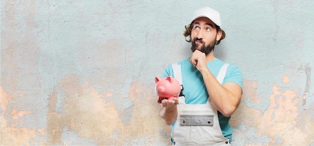 Professioneller maler mit einem sparschwein