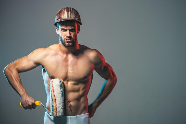 Professioneller maler muskulöser maler mann hält farbroller mann arbeiter in bauarbeiterhelm halten malerei