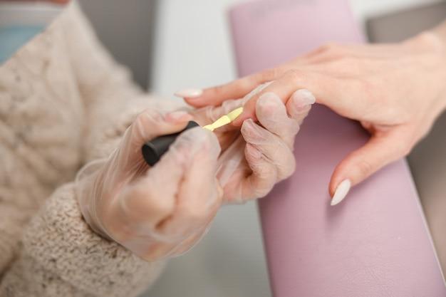Professioneller maniküre-meister, der nägel für glücklichen kunden im schönheitssalon tut