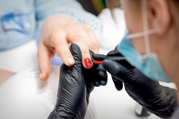 Professioneller maniküre-meister, der weibliche nägel durch roten nagellack im nagelstudio malt