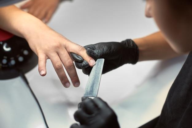 Professioneller manikürist, der an den fingernägeln des kunden arbeitet