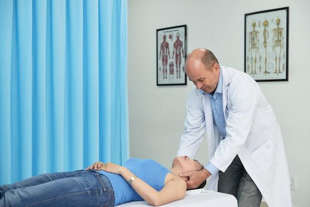 Professioneller manueller therapeut, der hals des patienten massiert