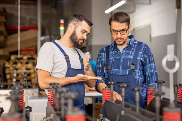 Professioneller maschinenbauingenieur, der seinem auszubildenden anweisungen gibt, während er in der werkstatt neue industrieanlagen zeigt
