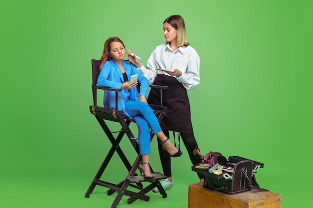 Professioneller maskenbildner, der make-up auf einem mädchen auf grünem studio tut