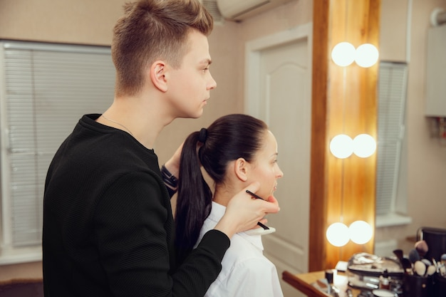 Professioneller maskenbildner, der mit schöner junger frau arbeitet. der mann im weiblichen beruf. konzept der gleichstellung der geschlechter