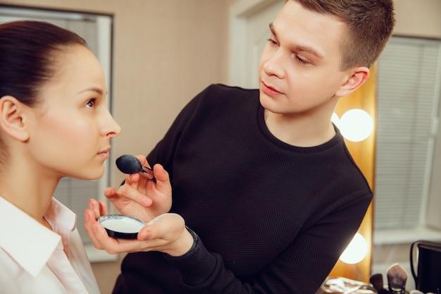 Professioneller maskenbildner, der mit schöner junger frau arbeitet.