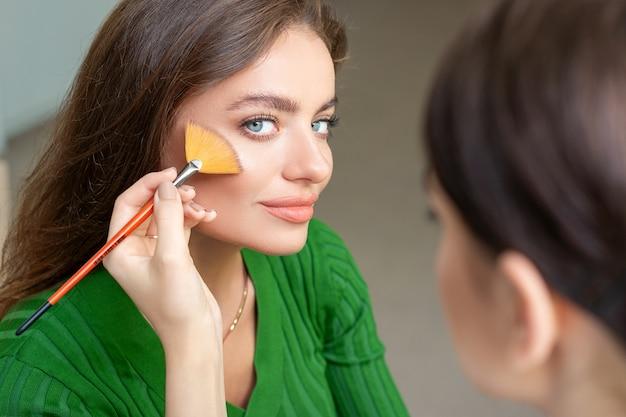 Professioneller maskenbildner, der puder durch pinsel auf wangen der schönen jungen kaukasischen frau im schönheitssalon anwendet