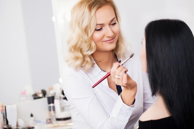 Professioneller maskenbildner, der vorbildliches make-up des zaubers bei der arbeit tut