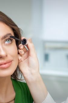 Professioneller maskenbildner, der wimperntusche auf wimpern der schönen jungen kaukasischen frau im schönheitssalon anwendet