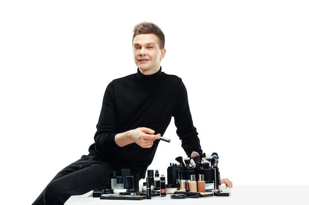 Professioneller maskenbildner mit werkzeugen lokalisiert auf weiß. der mann im frauenberuf. konzept der gleichstellung der geschlechter