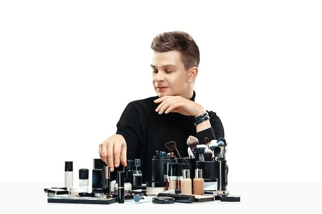 Professioneller maskenbildner mit werkzeugen lokalisiert auf weißem studiohintergrund. der mann im weiblichen beruf. konzept der gleichstellung der geschlechter