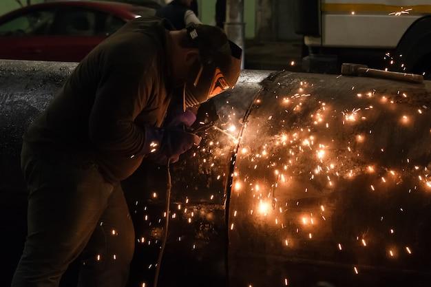 Professioneller maskengeschützter schweißer, der nachts an metallschweißen und metallfunken arbeitet. mitarbeiter schweißen stahl mit funken