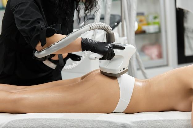 Professioneller masseur, der an der gesäßzone mit endosphärenvorrichtung auf kundin in weißem höschen arbeitet