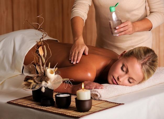 Professioneller masseur, der massageöl auf den weiblichen rücken im schönheitssalon aufträgt