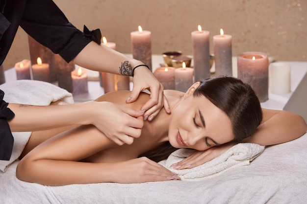 Professioneller masseur, der schultermassage für kundin im schönheitssalon mit kerzen tut