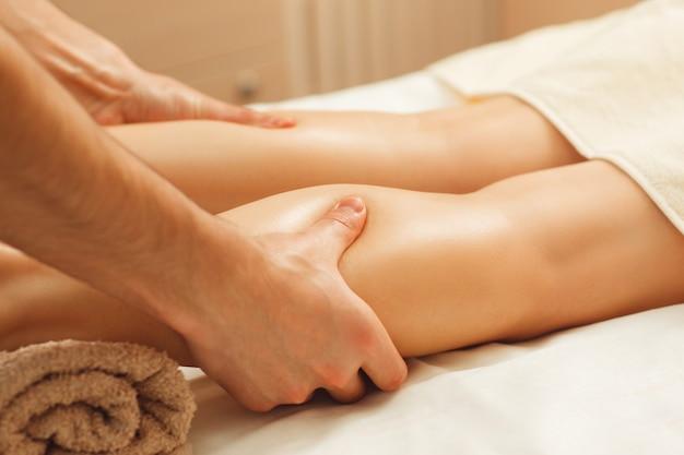 Professioneller masseur, der weibliche beine massiert