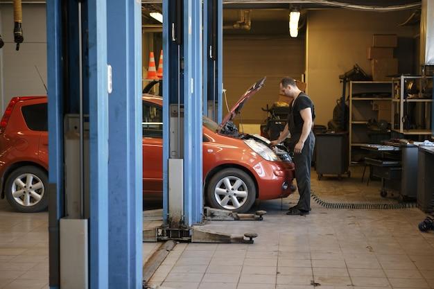 Professioneller mechaniker, der automotor in der garage repariert.