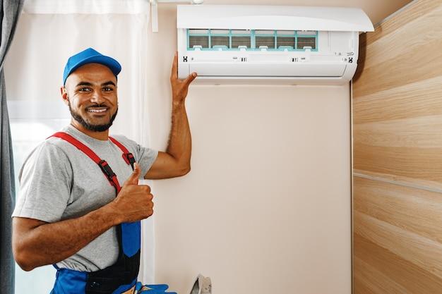 Professioneller mechaniker, der die klimaanlage in einem raum in der nähe installiert