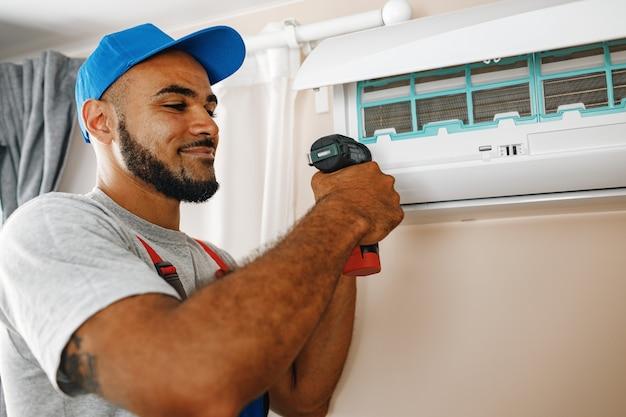 Professioneller mechaniker, der die klimaanlage in einem raum installiert
