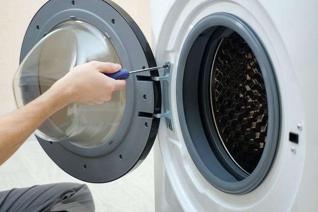 Professioneller mechaniker, der die schraube an der kaputten waschmaschinentür mit einem schraubendreher in der badezimmernahaufnahme verdreht