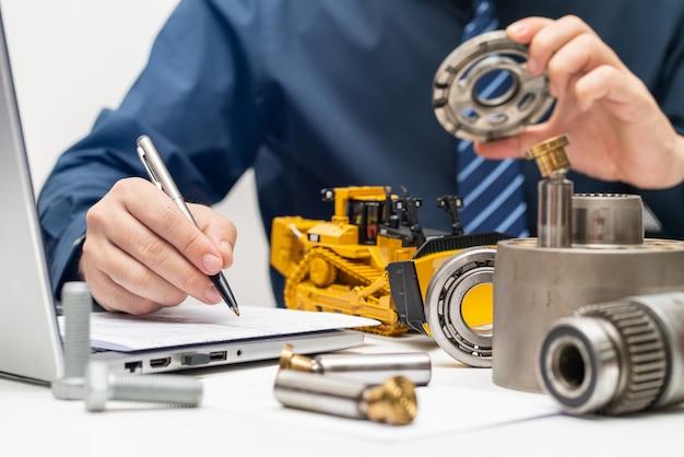 Professioneller mechaniker, der die ventilplatte der hydraulikkolbenpumpe inspiziert und berichte für den arbeitstag im büro schreibt, um das wartungskonzept für schwere maschinen zu reparieren