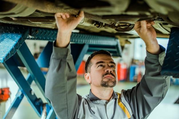 Professioneller mechaniker, der ein auto repariert.