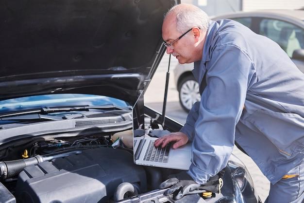 Professioneller mechaniker mit moderner technologie bei der arbeit