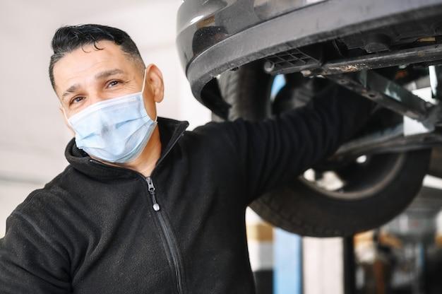 Professioneller mechaniker mit schützender gesichtsmaske, reparatur eines autos in der servicewerkstatt.