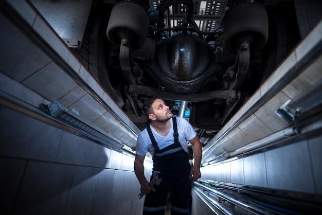 Professioneller mechaniker-servicetechniker unter dem lkw, der nach einem ölleck in der fahrzeugreparaturwerkstatt sucht