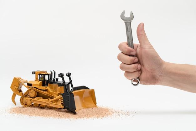 Professioneller mechanikermann, der schraubenschlüsselwerkzeuge mit bulldozer-traktormodell auf weißem hintergrund hält, repariert wartung schweres maschinenkonzept